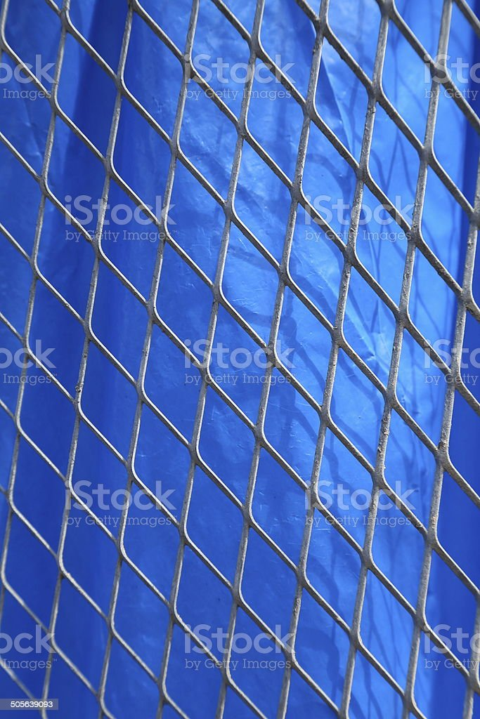 metal net on blue fabric background royalty-free stock photo