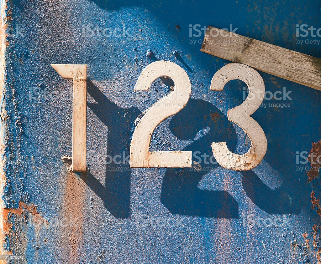 Metal  numbers on eroded mental plate in the sun stock photo