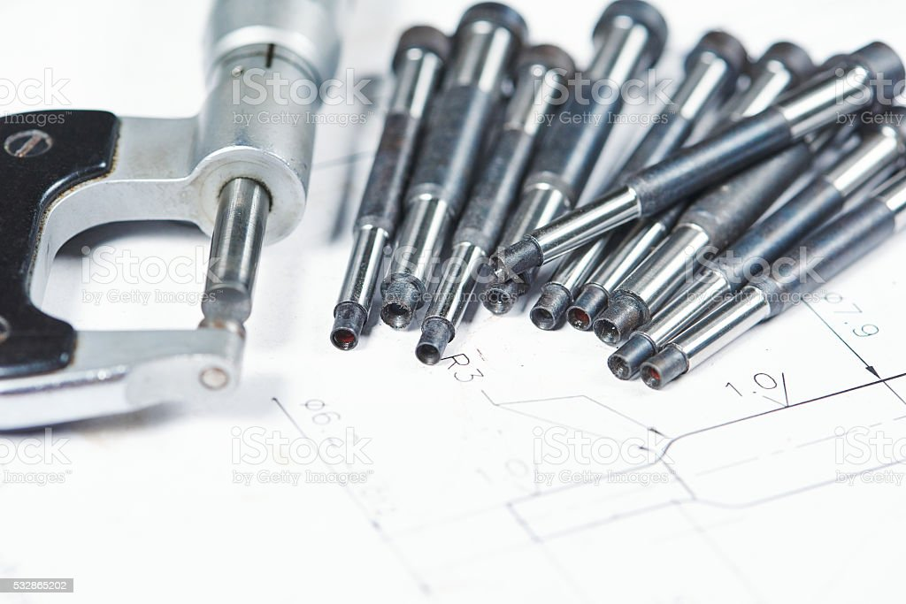 metal part machining. Details with measuring micrometer on print drawing stock photo