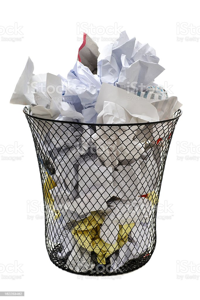 Metal patterned waste basket overflowing with crumpled paper stock photo