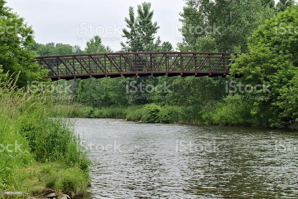 Metal pedestrian bridge over river royalty-free stock photo