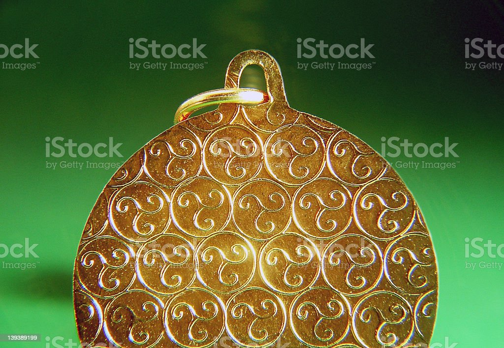 Metal pendant with Triskele pattern stock photo