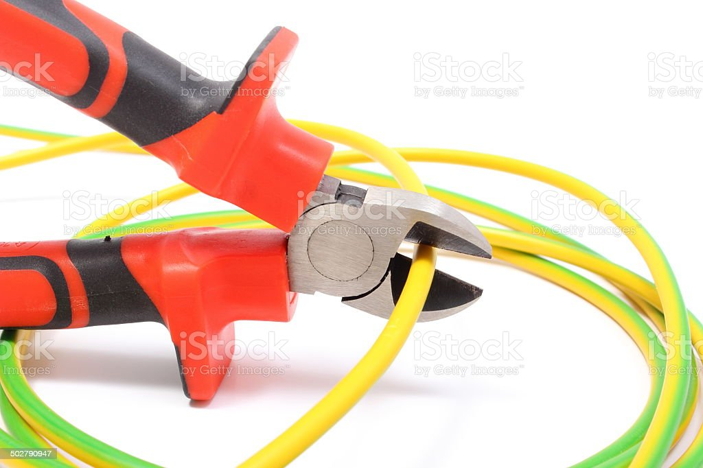 Metal pliers and green-yellow cable on white background stock photo