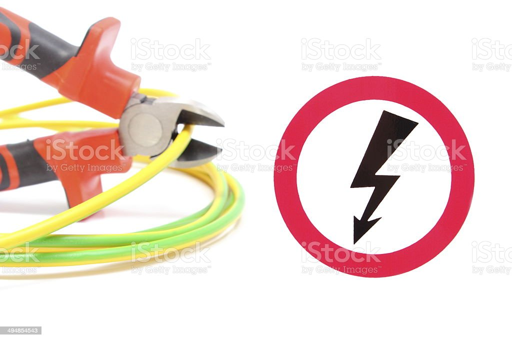 Metal pliers, green-yellow cable and high voltage danger sign stock photo