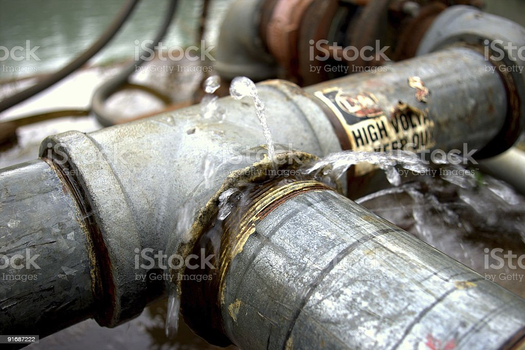 A metal plumbing pipe that is leaking water royalty-free stock photo