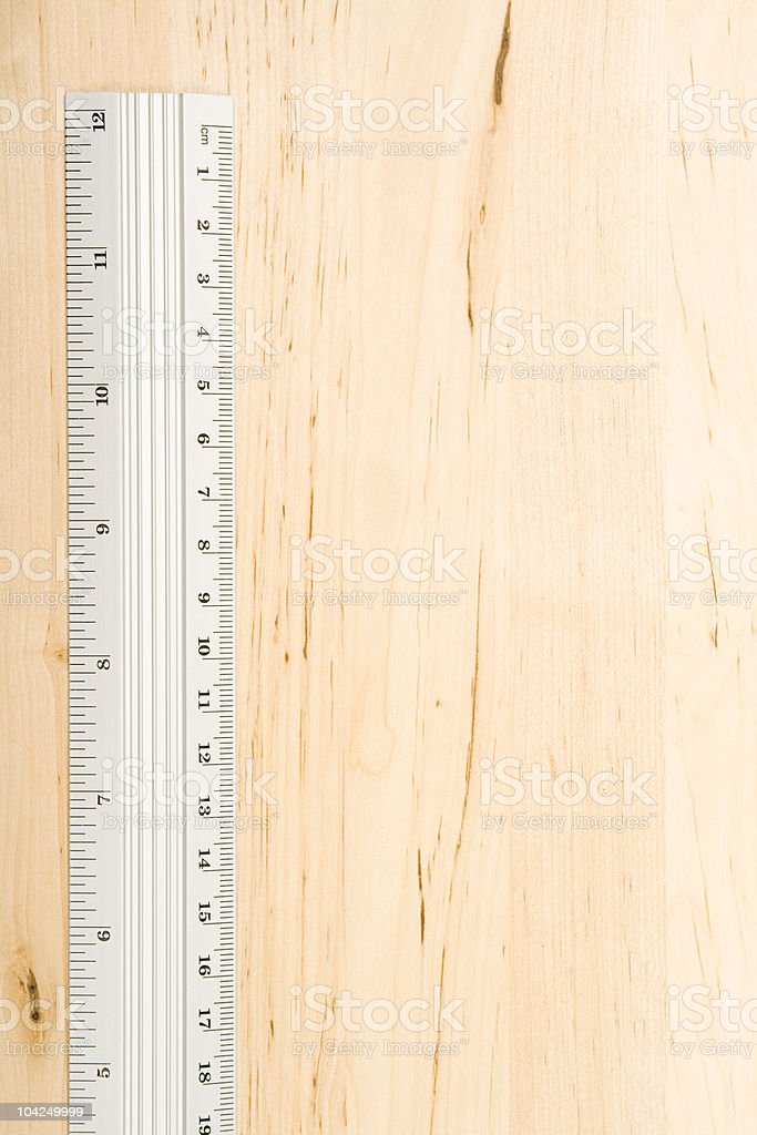 Metal ruler on wood background. royalty-free stock photo