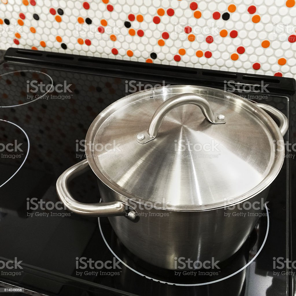 Metal saucepan on a stove stock photo