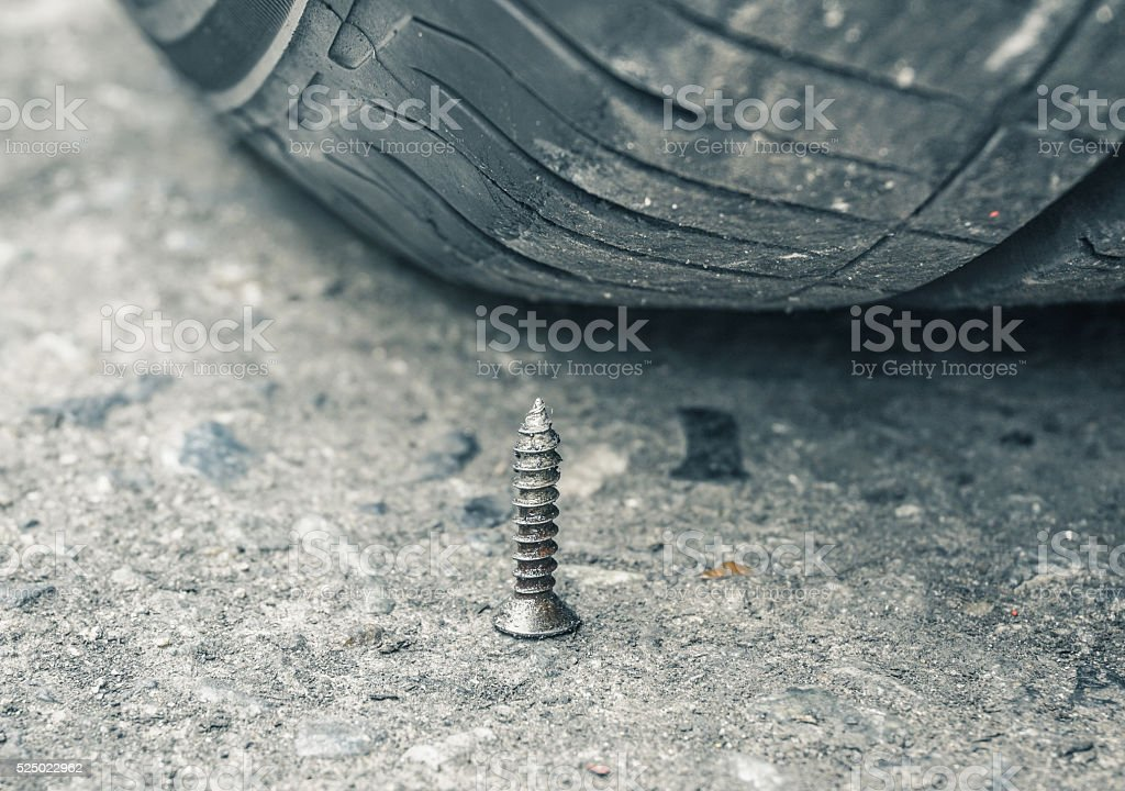 Metal spike and tire stock photo