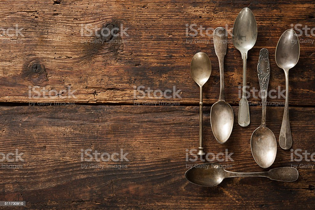 Metal spoons on wooden table stock photo
