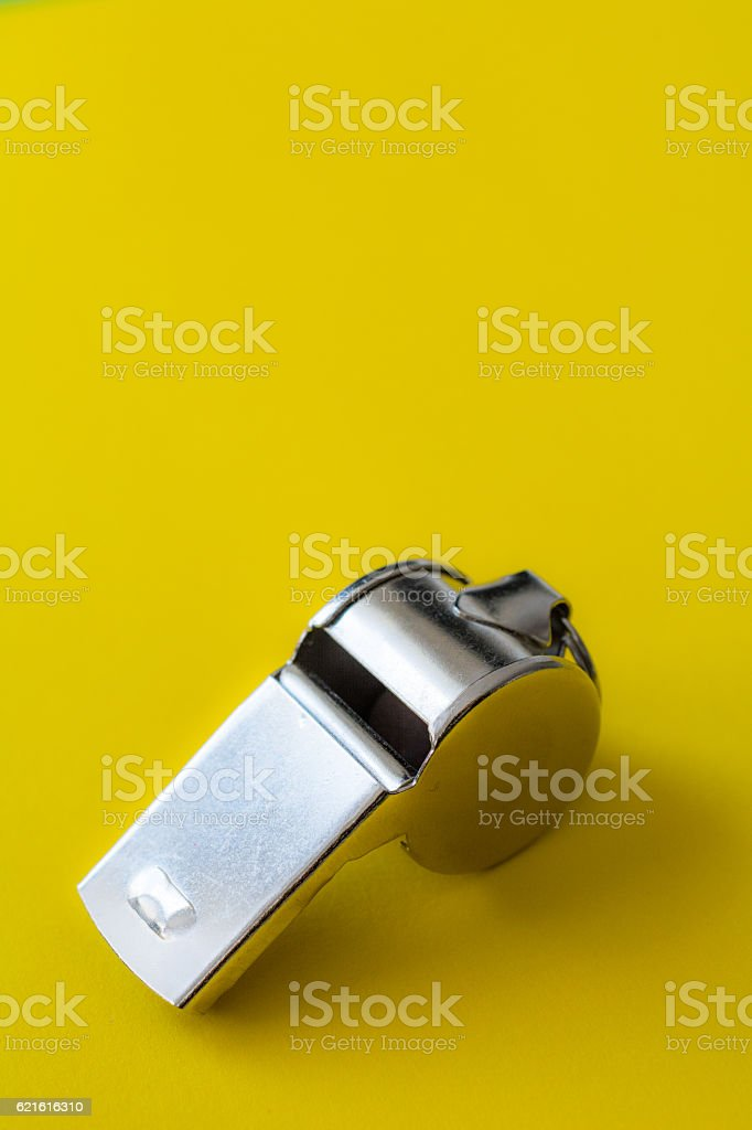 Metal sports Whistle on yellow paper stock photo