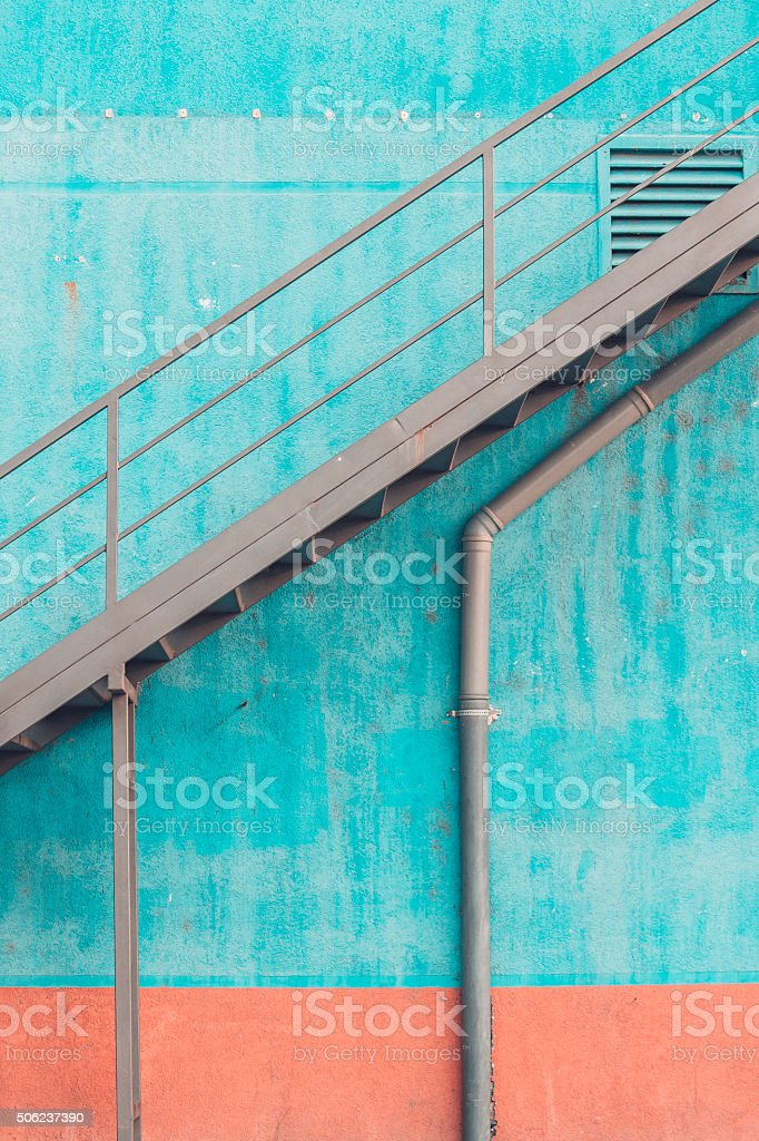 Metal staircase on blue wall stock photo