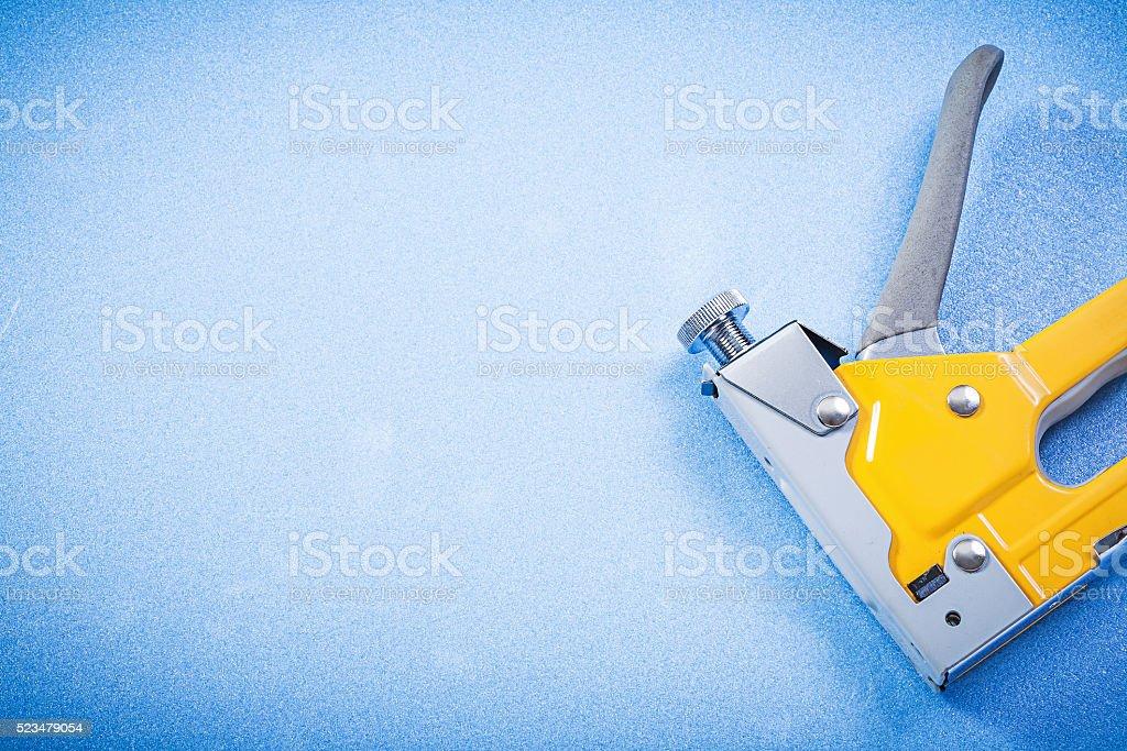Metal staple gun on blue background construction concept stock photo
