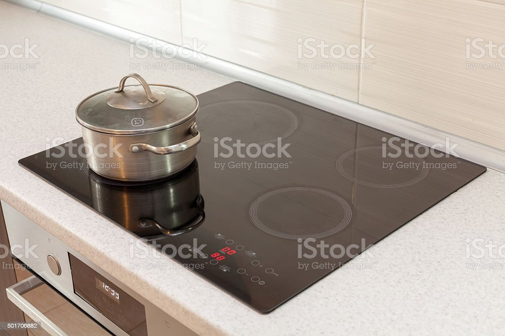 Metal steel saucepan in modern kitchen with induction stove stock photo