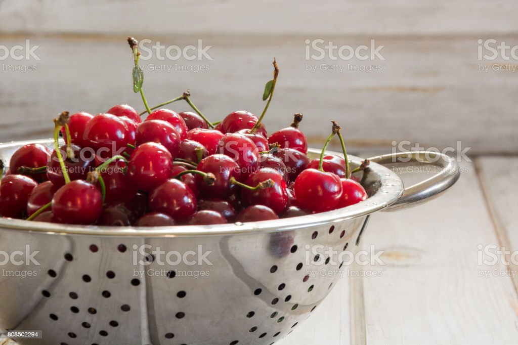Metal strainer or bowl with ripe berries and cherry on wooden background. Colander filled with fresh cherries over a rustic board with copy space. stock photo