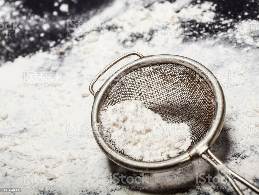 Metal strainer with spilling flour stock photo