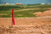 Metal survey peg with red flag on construction site