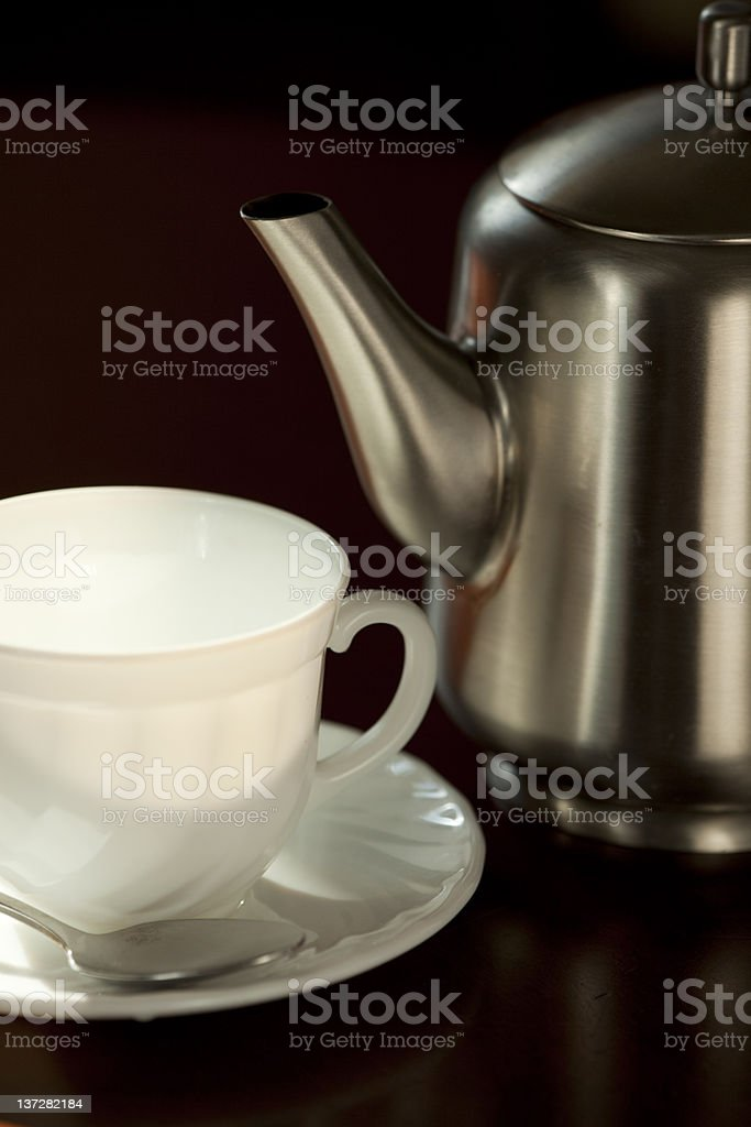 Metal teapot and the white cup  with saucer royalty-free stock photo