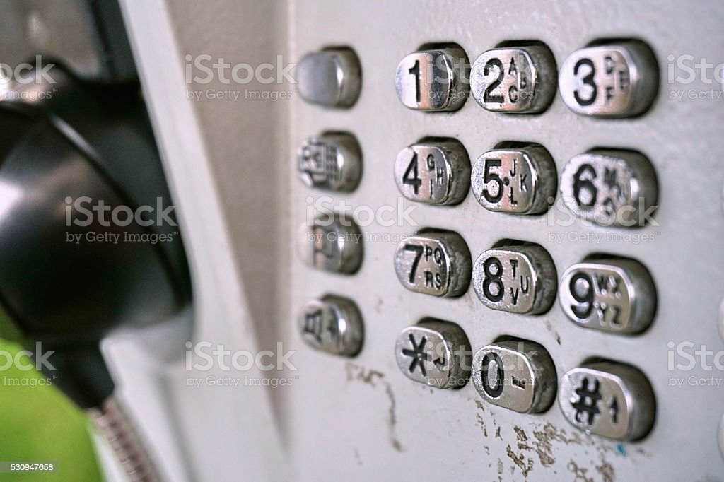Metal telephone dial in the public phone booth stock photo