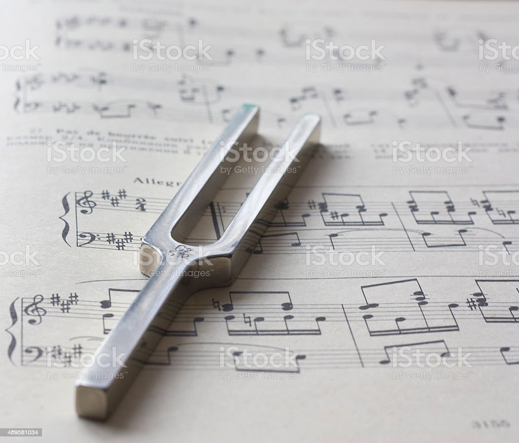 Metal tuning pitchfork on top of musical sheets stock photo