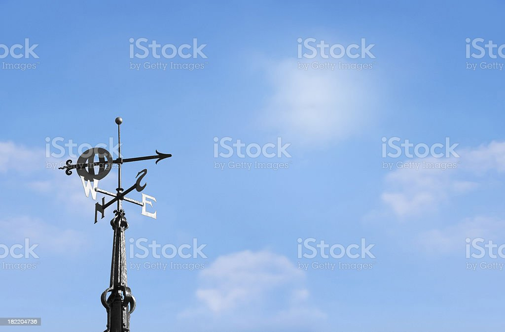 Metal weather vane pointing south against blue sky stock photo