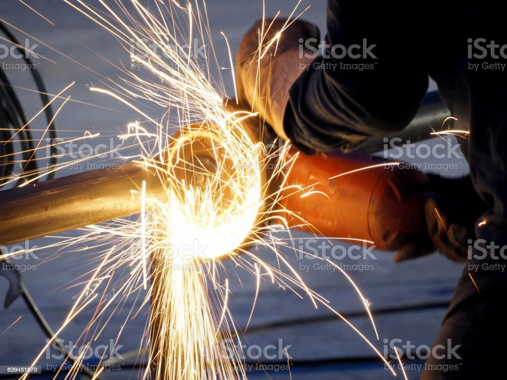 Metal worker in a factory grinding with sparks stock photo