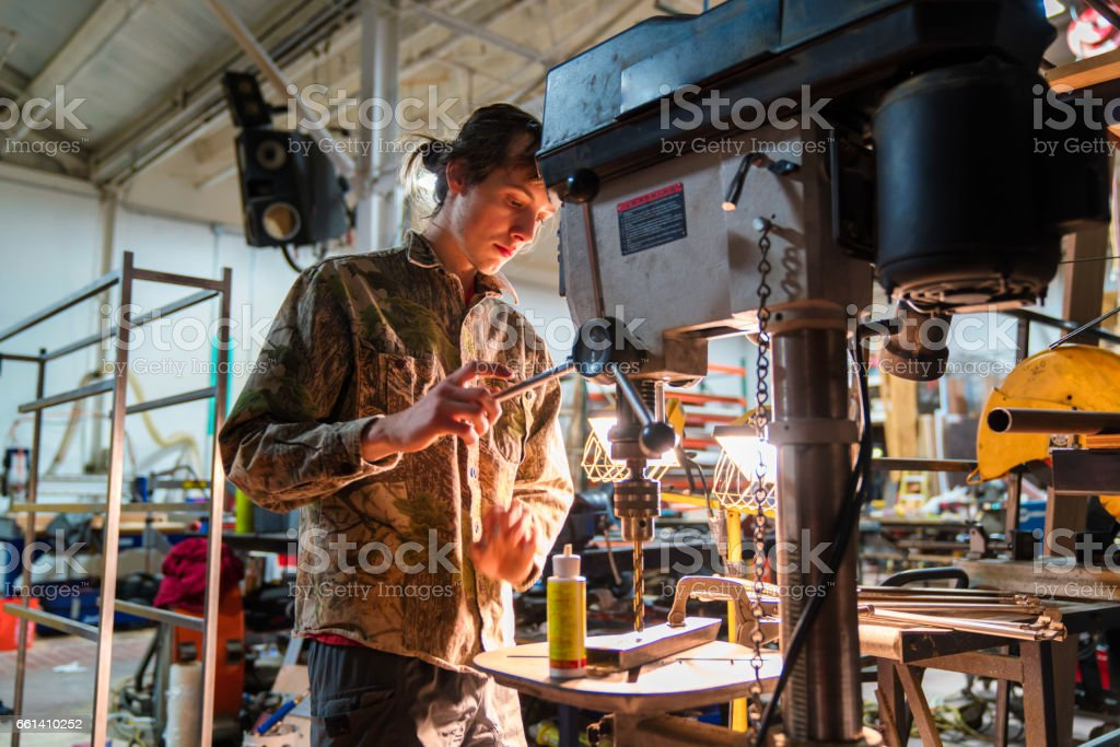 Metal worker using a drill press in a workshop stock photo