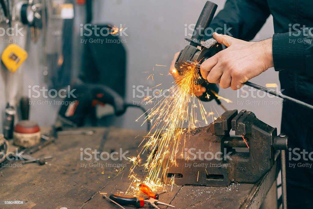 Metal worker using grinder. stock photo