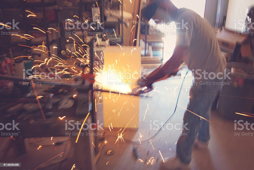 Metal worker with circular saw in small workshop stock photo