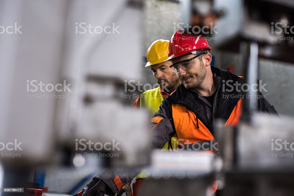 Metal workers cooperating while working in aluminum mill. stock photo