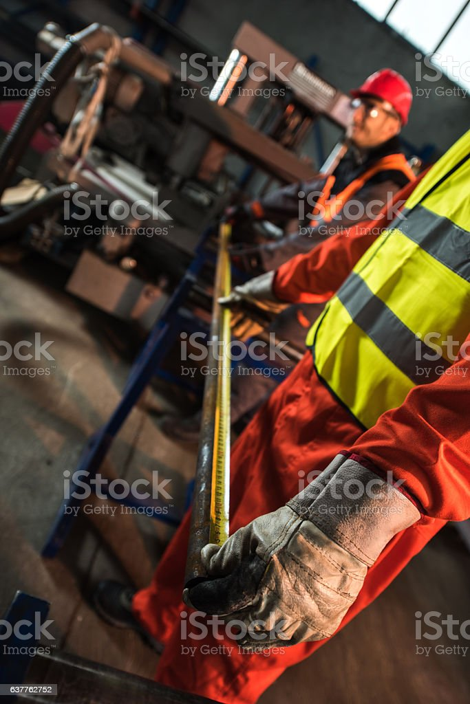 Metal workers measuring steel in an aluminum mill. stock photo