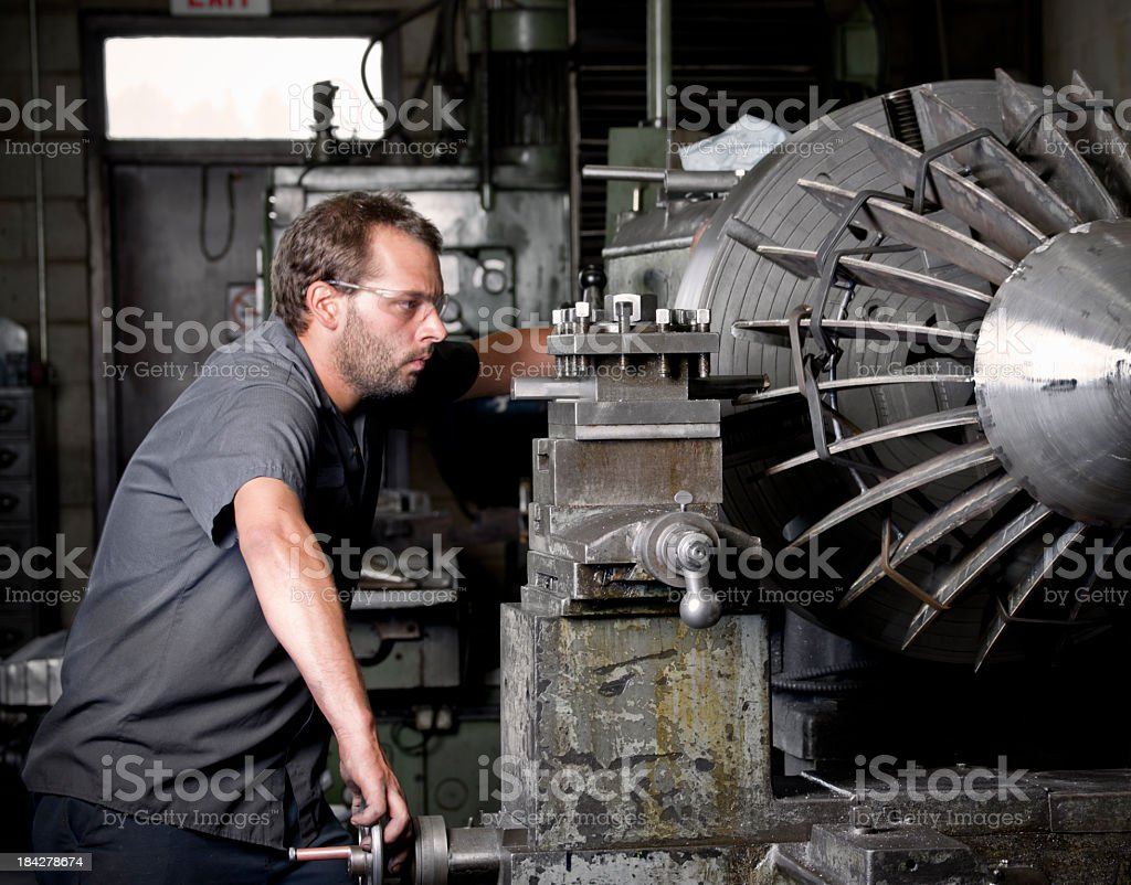 Metal working machinist operating an industrial lathe stock photo