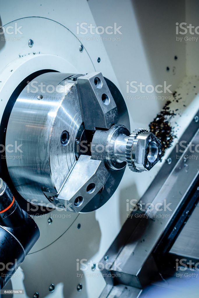 metal workpiece clamped in the lathe chuck CNC machine stock photo