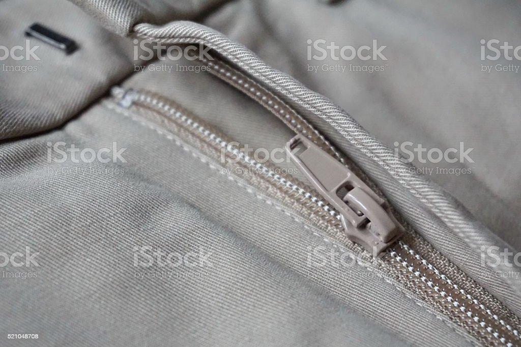 Metal zipper sliding on the fine gray (beige) pants stock photo