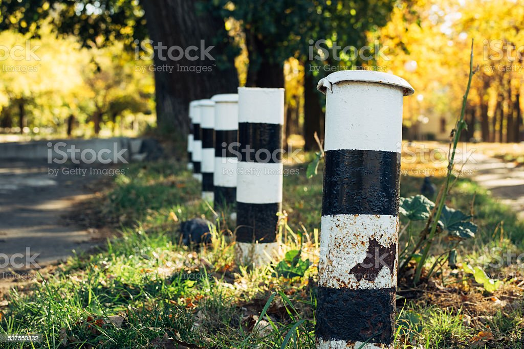 Metallic black and white poles fence at the roadside stock photo