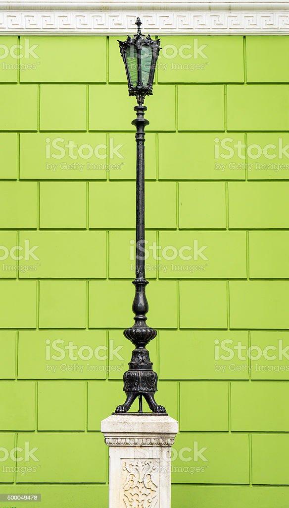 Metallic black lamppost on green brick wall background stock photo