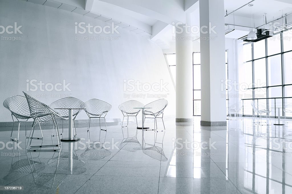 Metallic chairs in an empty white meeting room stock photo
