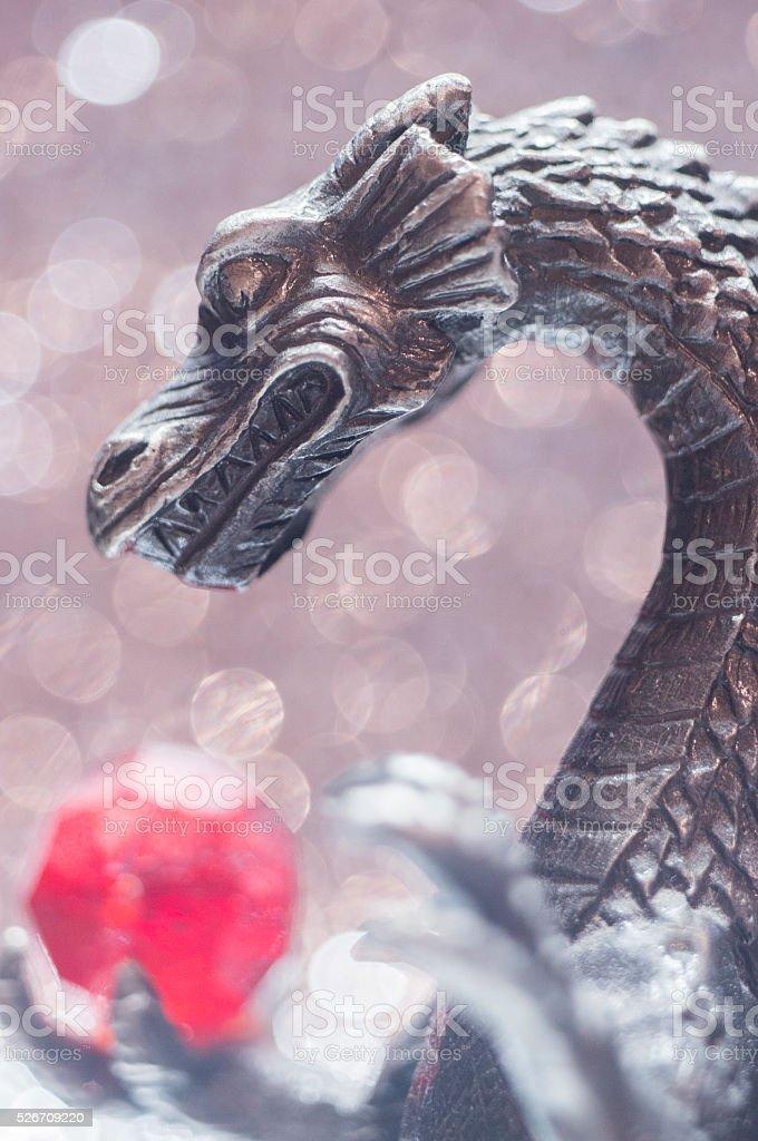 Metallic dragon holding a bead stock photo