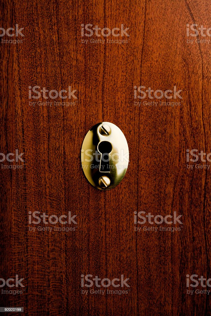 A metallic keyhole on a wooden door stock photo