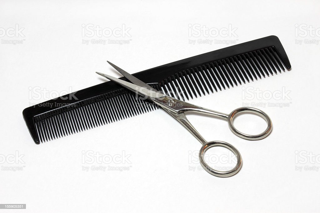 Metallic scissors over a simple black comb isolated in white stock photo