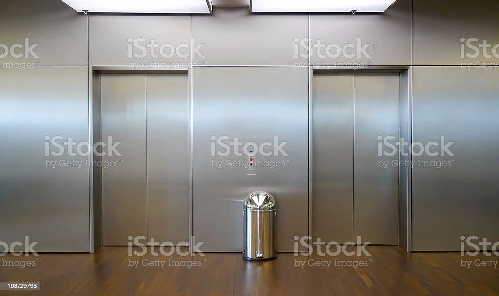 Metallic trash bin in between two elevator doors royalty-free stock photo