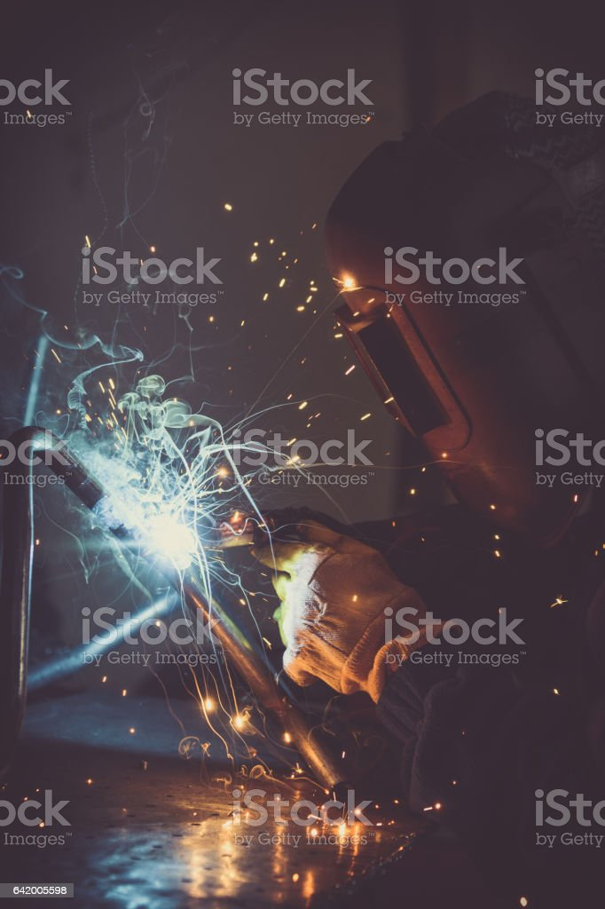 Metalwork industry background of man welding loops of steel pipe, generating sparks, smoke and reflexions stock photo