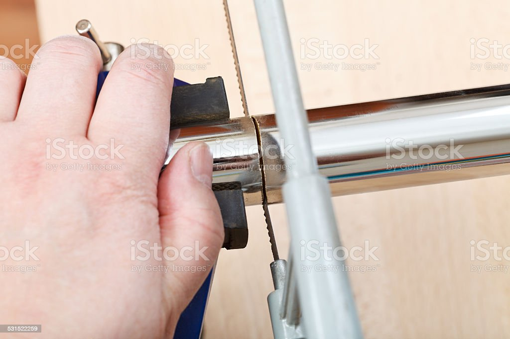 metalworker saws metal pipe close up stock photo