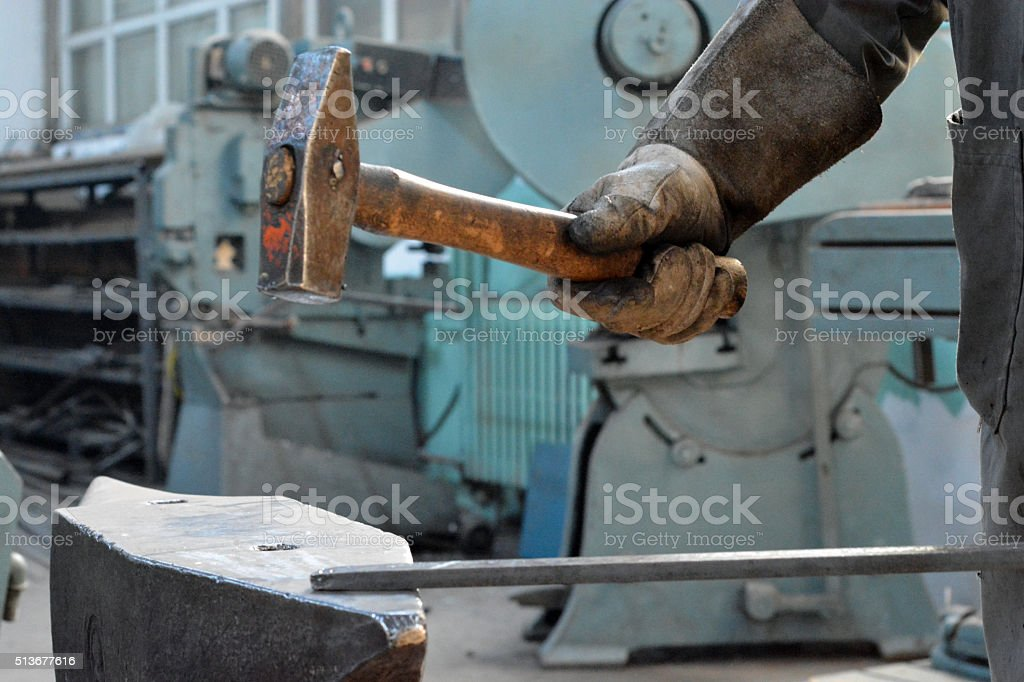 metalworker works metal with hammer on the anvil stock photo