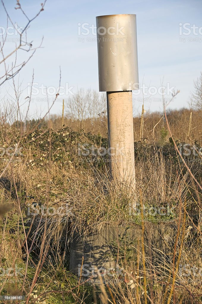 Methane gas exhaust pipe in old landfill royalty-free stock photo