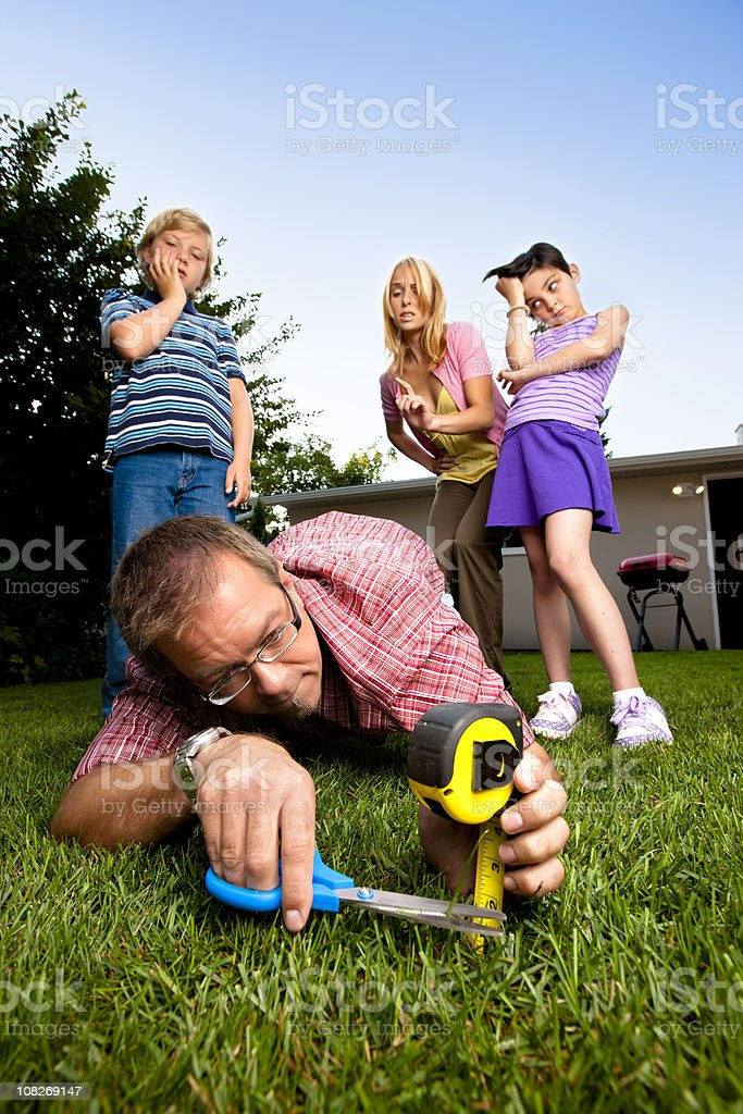 Meticulous Father Mowing the Lawn with Scissors stock photo
