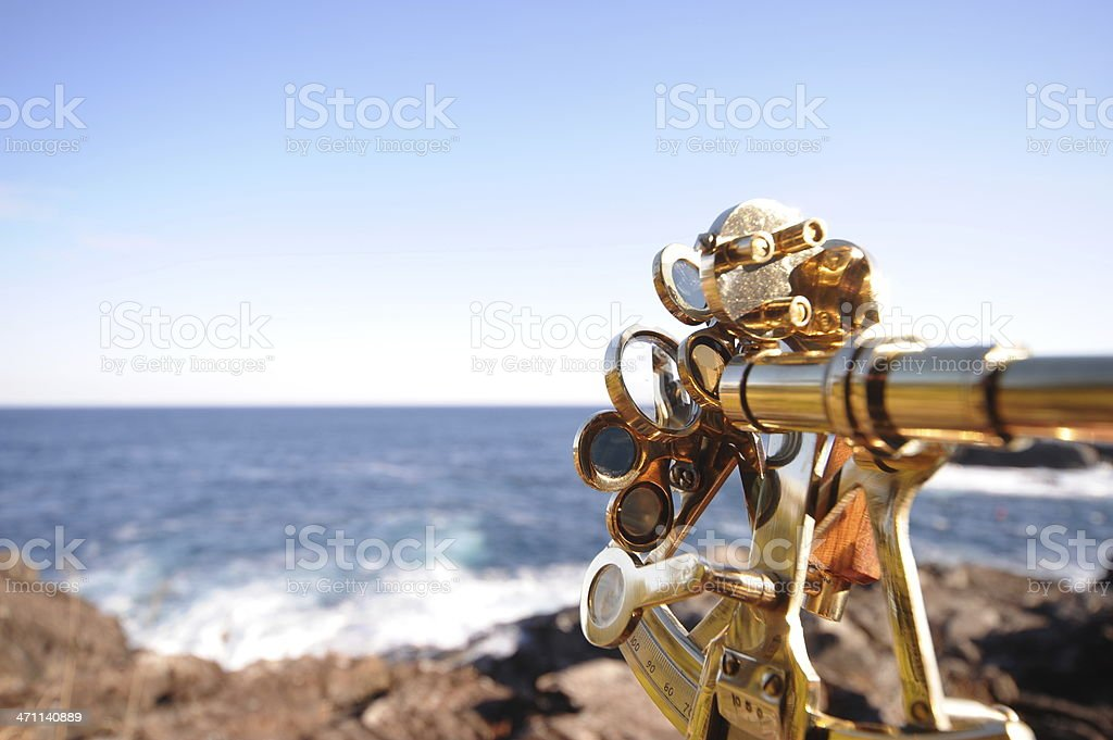 Meticulous measuring tool, a sextant, facing ocean water stock photo