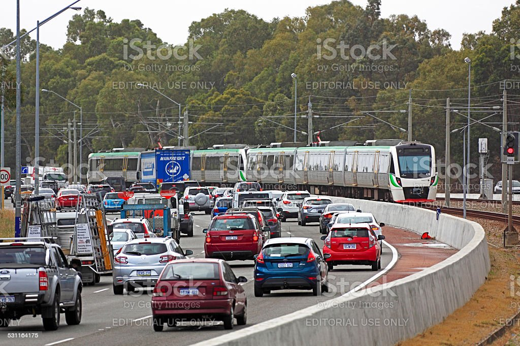 Metro train running down the middle of a congested freeway stock photo