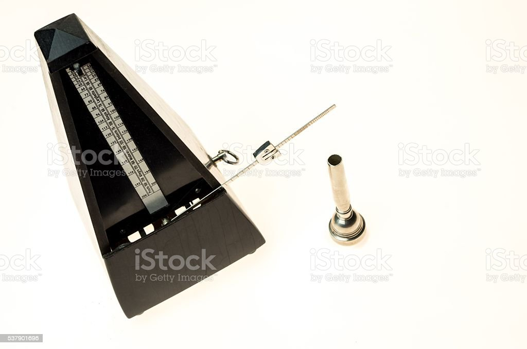 Metronome and mouthpiece of a trumpet isolated stock photo
