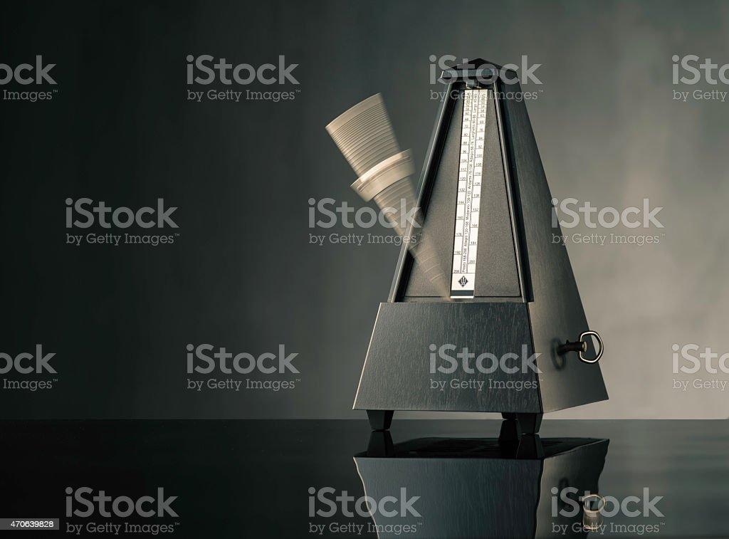 Metronome on grey background - horizontal stock photo