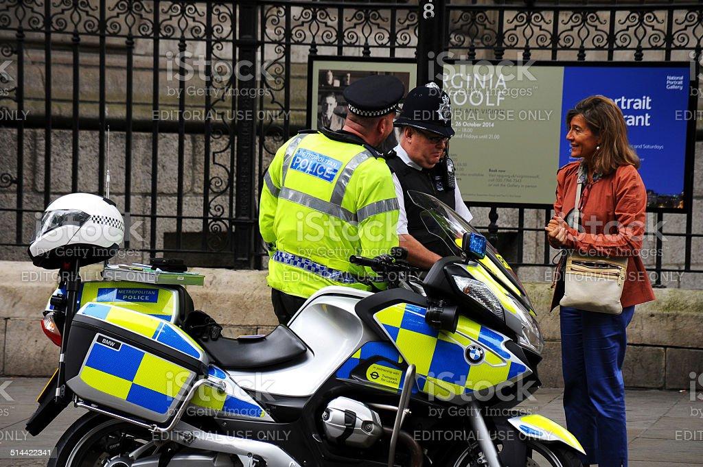 metropolitan police patrol to advise a woman on the street stock photo